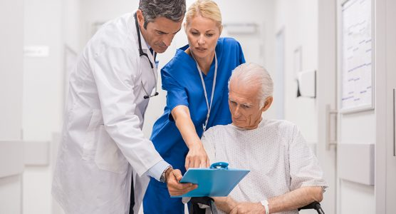 Doctor and nurse with senior patient in wheelchair at hospital corridor talking. Mature doctor showing and discussing medical report with nurse and senior disabled at medical clinic.